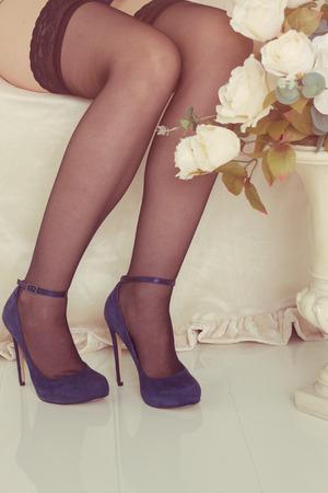 bas r�sille: Attractive jambes sur le lit blanc avec des bas r�sille et chaussures � talons.