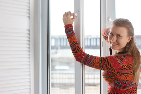 Woman opens a plastic window and smiling