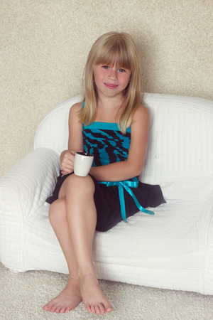 beautiful preteen girl: Girl 5 years old sitting on a sofa with cup