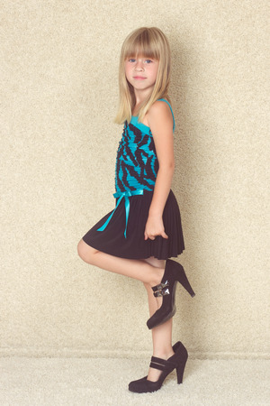girl 5 years old in big shoes with heels photo