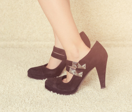 Baby foot in women high-heeled shoes photo