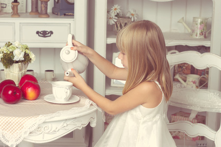 Little girl sitting at the table with fruits and teapot photo