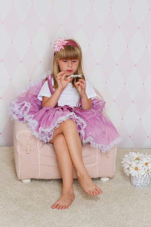 Little girl princess is sitting on chair photo