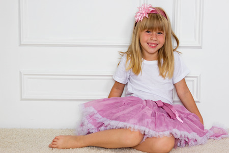 pink posing: Little girl in a beautiful dress sits near a wall Stock Photo