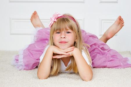 Beautiful girl lying on floor studio shot Standard-Bild