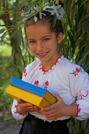 drover: Beautiful little girl 7 years in embroidery books in color Ukrainian flag