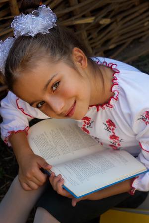 top 7: Hermosa ni�a de 7 a�os en los libros de bordado. vista superior Foto de archivo