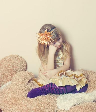 Sad young girl sitting Фото со стока