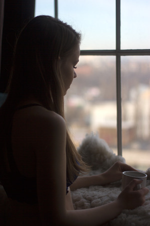 Woman in the morning. woman with neat body is holding a cup with hot tea or coffee and looking at the sunrise standing near the window in her home and having a perfect cozy morning photo
