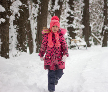 pink hat: Little girl in winter pink hat in snow.