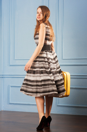 Girl in a magnificent dress with a yellow suitcase standing near blue wall