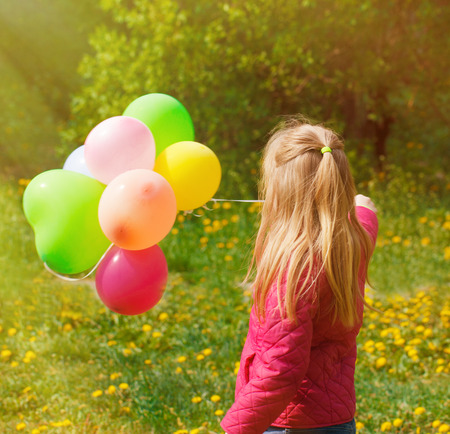 turn away: Outdoor portrait of a cute young  little girl Turned back with balloons