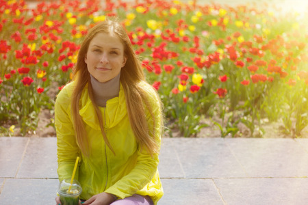 blond girl sitting next to a flower bed photo