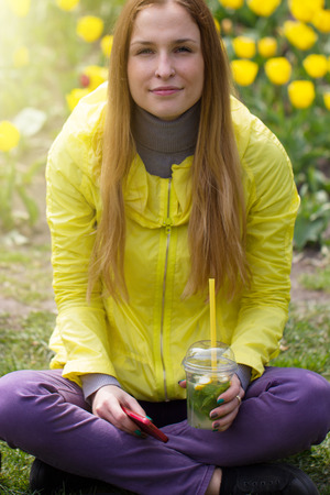 Beautiful girl holding a lemonade in outdoor photo