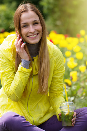 Woman calling on the mobile phone in a green field with yellow flowers photo