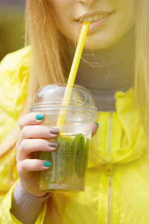 girl is drinking a large glass of lemonade. Close portrait photo