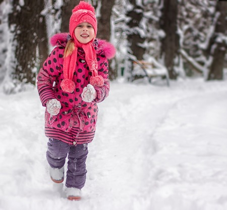 5 year old: Happy 5 year old girl running on snow-covered park