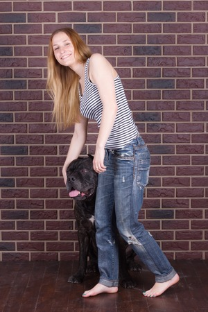 cane corso: girl in jeans  standing near the wall and hugging a big dog Cane Corso
