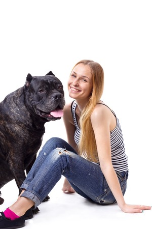 cane corso: girl sitting and smile  next to his dog Cane Corso. isolate
