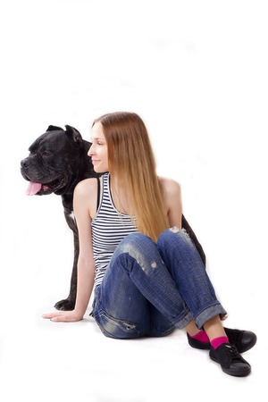 cane corso: girl sits on the floor. Her dog Cane Corso sitting at her. Look in the side. isolate