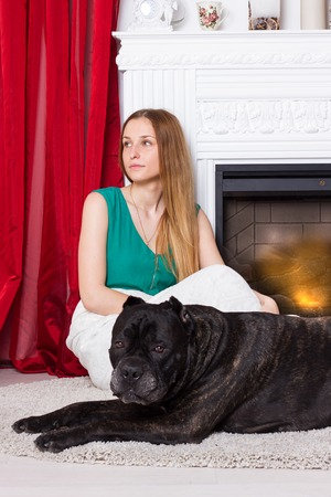 cane corso: Girl in green dress sitting by the fireplace with a dog Cane Corso Stock Photo