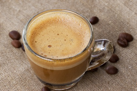cappuccino cup: Cappuccino with crema in a transparent cup on sacking. with coffee beans close