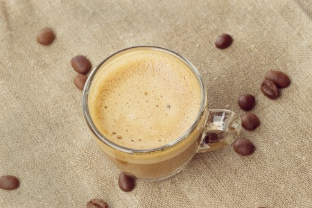 crema: Cappuccino with crema in a transparent cup on sacking. with coffee beans close. toning Stock Photo