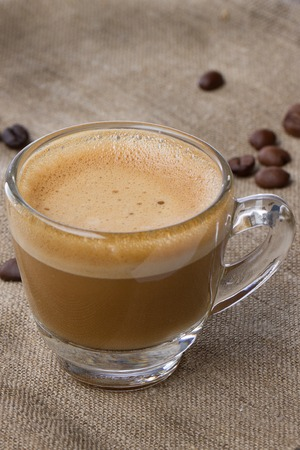 crema: Cappuccino with crema in a transparent cup on sacking. with coffee beans close vertical framing Stock Photo