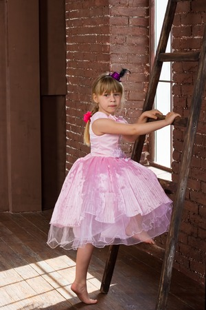 6 years girl: Girl 6 years old climbs a ladder in the room Stock Photo