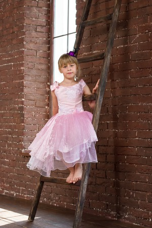 6 years girl: Girl 6 years old sitting on the ladder in the room Stock Photo