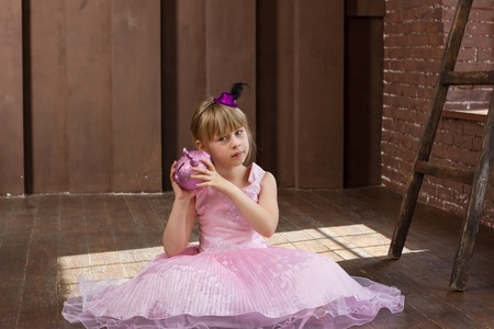 6 years: Girl 6 years old in a pink dress with a piggy bank in her hands Stock Photo