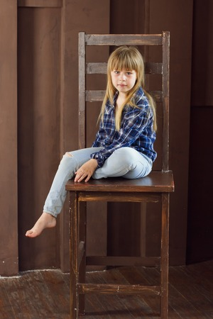 Girl 6 years old in jeans and a blue shirt is sitting on a high chair in a room with brown walls