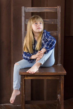 unwound: Girl 6 years old in jeans and shirt is sitting on a high chair in a room with brown walls