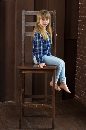 Girl 6 years old sitting on a high chair in a room with brown walls Stock Photo
