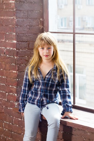 6 years girl: Girl 6 years old in jeans sitting on the windowsill
