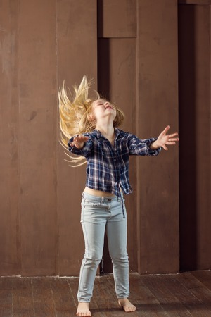 expressive: Girl 6 years old in jeans expressive dancing. Hair fluttering
