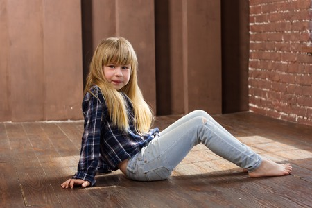 little blonde girl: Girl 6 years old in jeans sitting on the floor