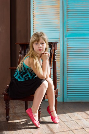 6 year old: Girl 6 years old in a dress sits on a chair near the blue wall