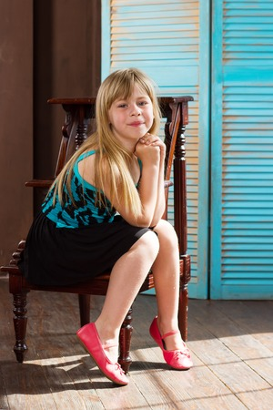 6 years girl: Girl 6 years old in dress sits on a chair near the blue wall