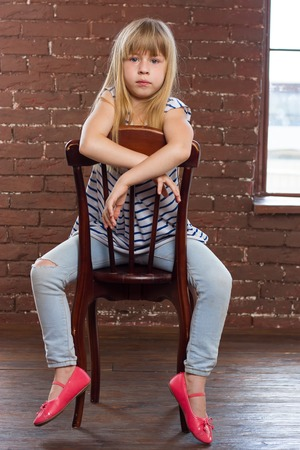 sits on a chair: Girl 6 years old in jeans sits on a chair Stock Photo