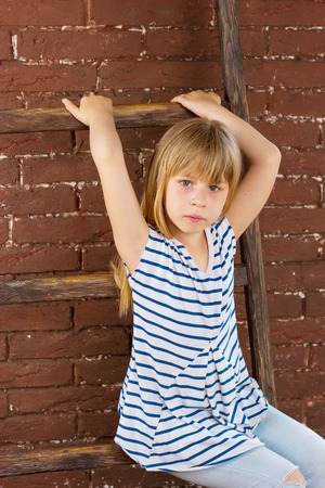 6 years girl: Girl 6 years old in jeans and a vest sits on a ladder near a brick wall