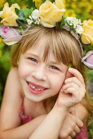 lacks: Girl 6 years old in a wreath closeup. Smiles. Baby teeth fall out. Stock Photo