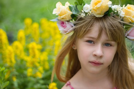 6 years girl: Girl 6 years old in a wreath close-up against a landscape
