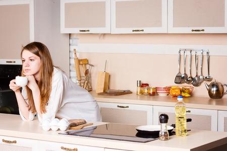 breakfast room: Girl thinking drinking tea in the kitchen Stock Photo