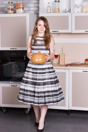 ordinary: Happy ordinary woman with pan at her kitchen