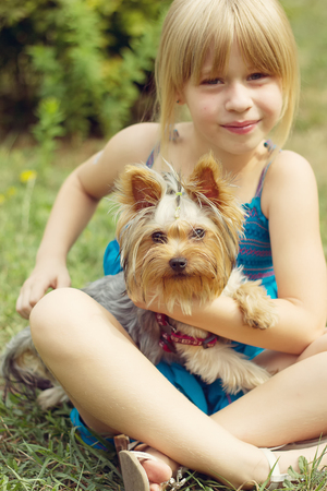 6 years: Girl 6 years old on the grass holding a Yorkshire Terrier