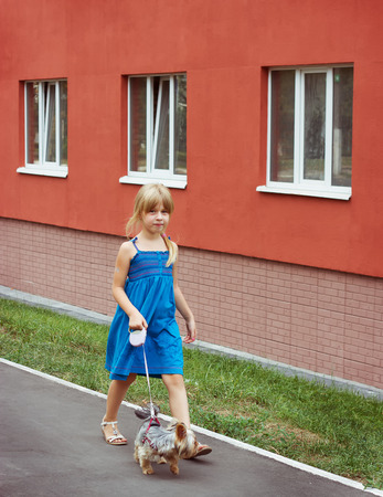 6 years: Girl 6 years old walking with a Yorkshire terrier near a high-rise building