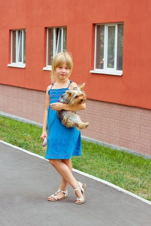 6 years: Girl 6 years with Yorkshire terrier in her arms near a high-rise building Stock Photo