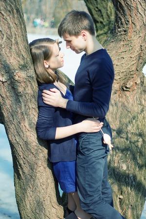 kiss love: Romantic Teenage Couple By Tree In Autumn Park Stock Photo