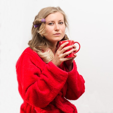 Half-length portrait of pretty young housewife wearing curlers and  wrapper holding red cup of tea having a rest photo